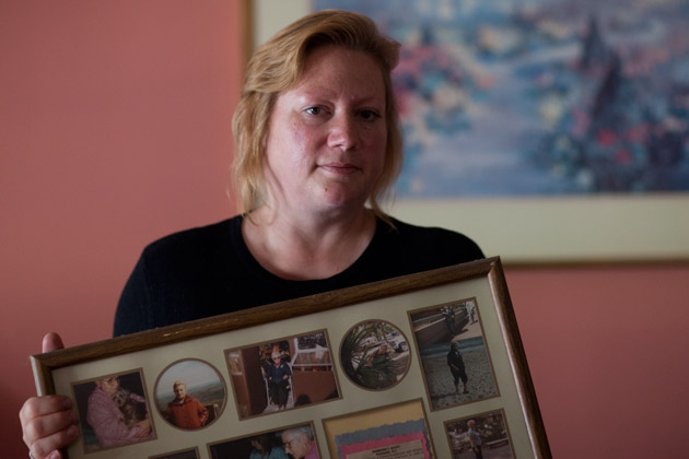 Cathleen Sharkey holds a frame of photographs of her mother, Barbara Scott, whose bloodline became disconnected during a dialysis treatment at Dutchess Dialysis Center. Scott never fully recovered and died shortly after of heart failure. (Dan Nguyen/ProPublica)